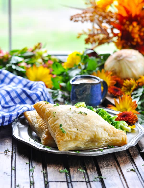 Turkey Pot Pie pockets on plate with gravy and flowers in background