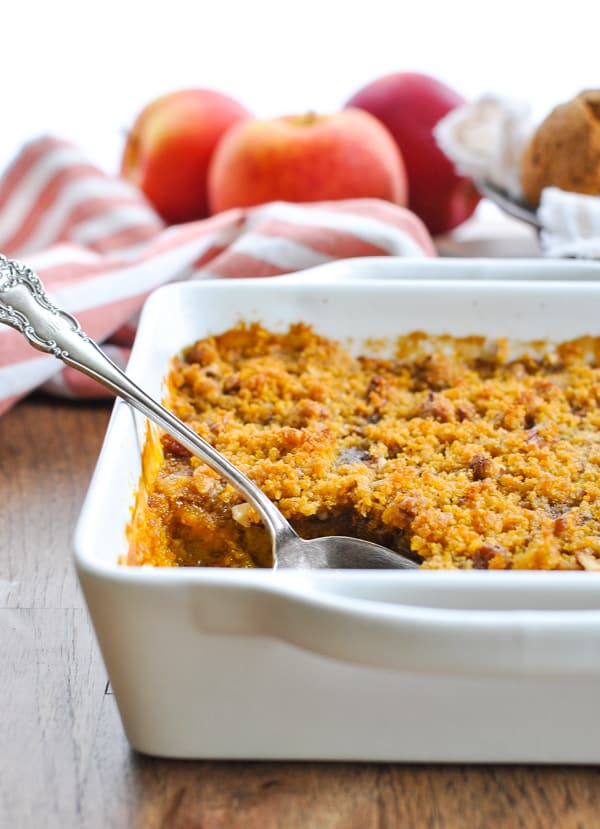White casserole dish with southern sweet potato casserole topped with pecans