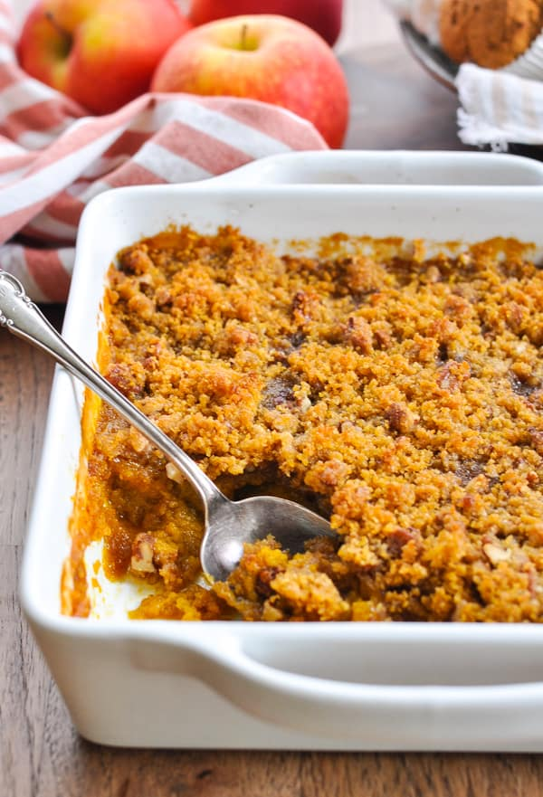 White baking dish with southern sweet potato casserole and a silver spoon inside