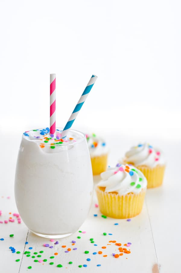 Glass of cake batter healthy smoothie recipe with cupcakes in background