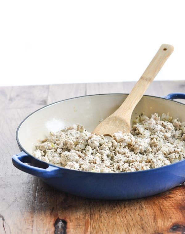 Cooked ground turkey in a skillet with wooden spoon