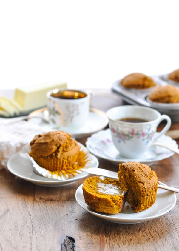Pumpkin muffin on a plate cut in half with butter