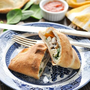 Chicken and Spinach Calzone recipe cut in half on a plate