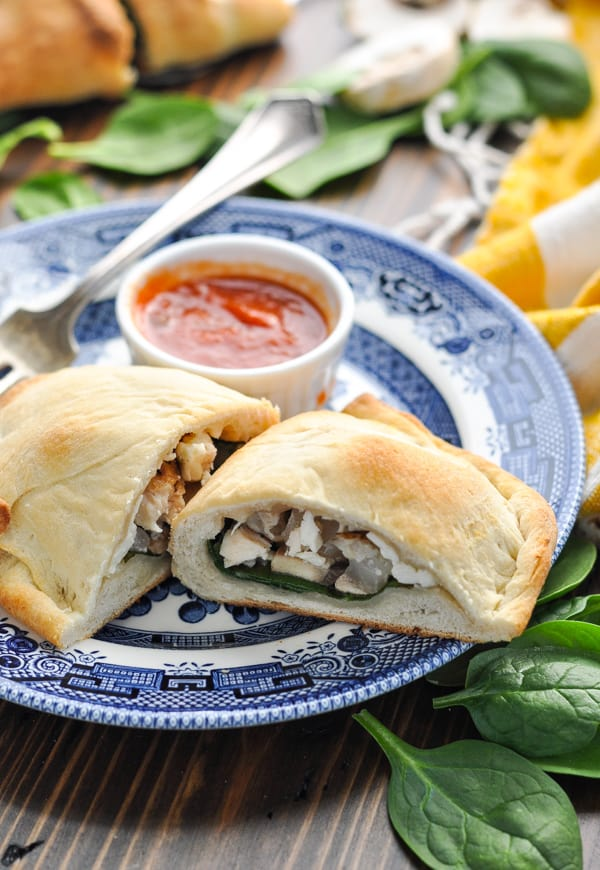 Close up front shot of chicken and spinach calzone on a blue and white plate