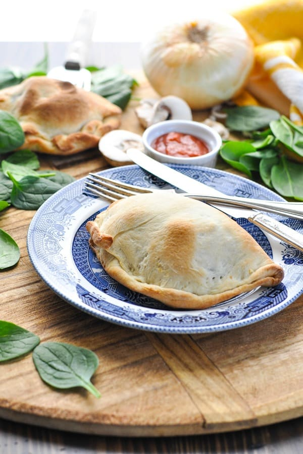 Baked calzone on a plate with knife and fork