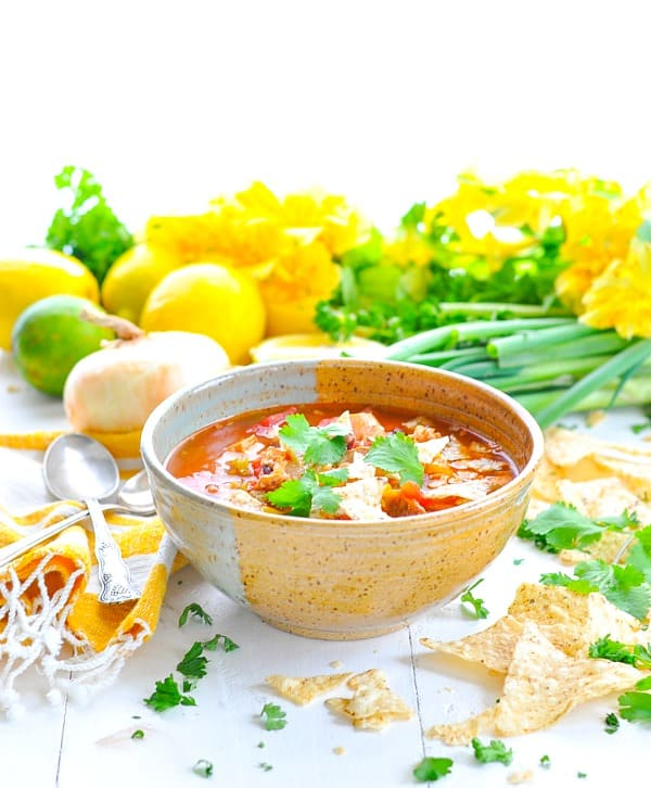A bowl of easy chicken tortilla soup on a white surface with tortilla chips and chopped herbs scattered around