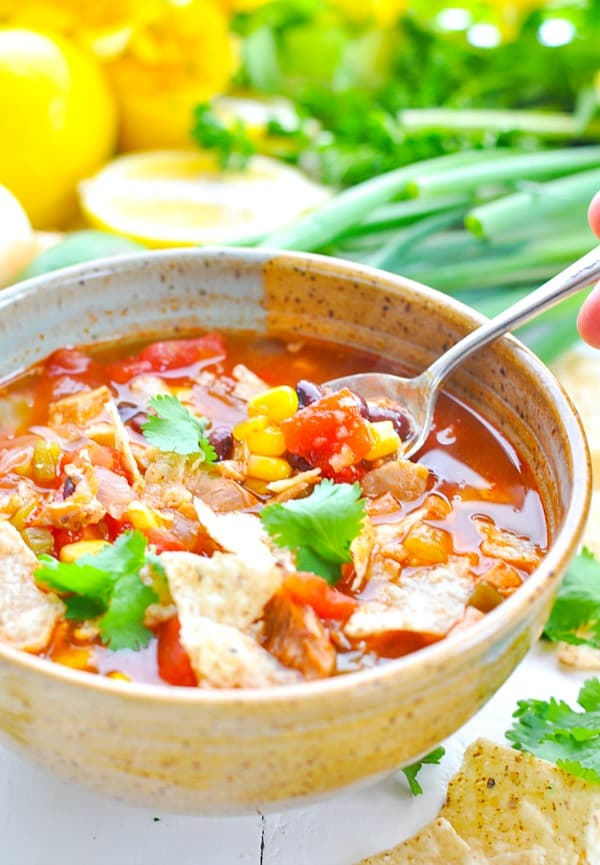 A bowl of easy chicken tortilla soup with a spoon scooping out some corn, beans and tomatoes