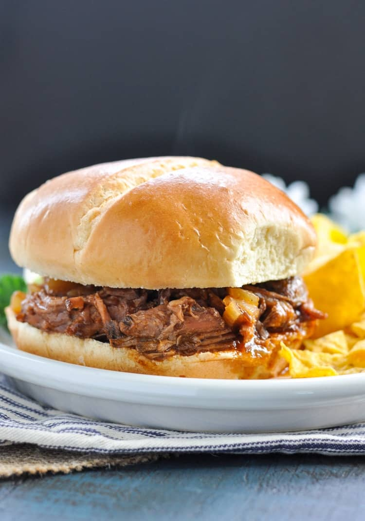 Slow cooker beef BBQ on a bun with a side of chips