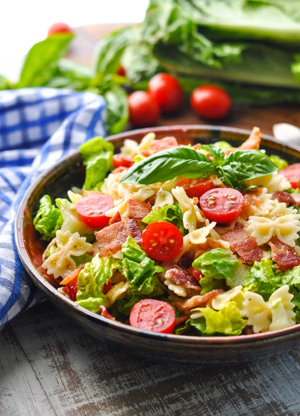 Side shot of a BLT pasta salad in a bowl garnished with basil
