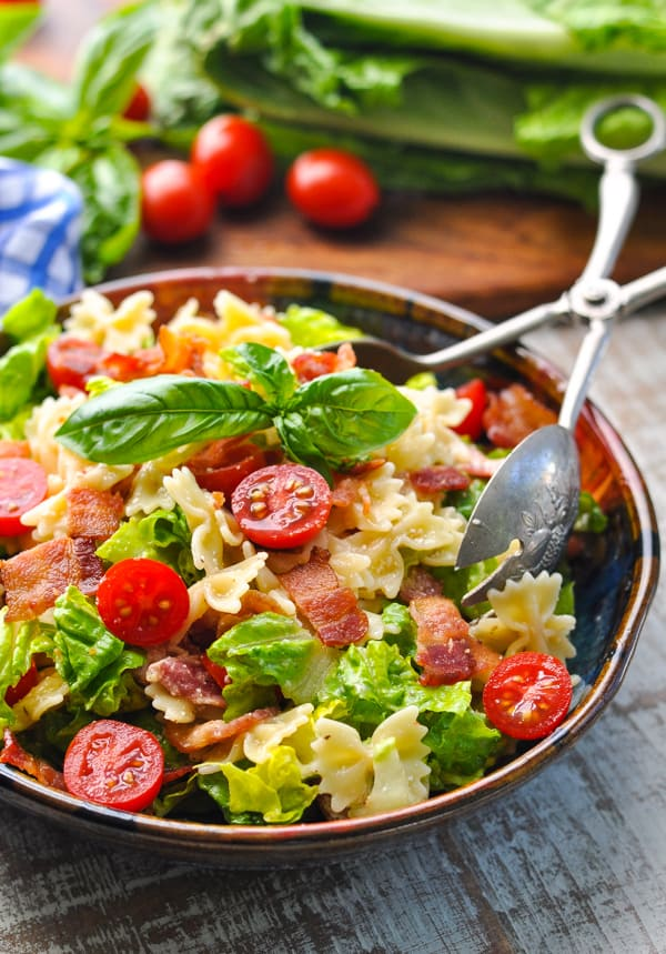 A BLT pasta salad in a bowl with serving spoons