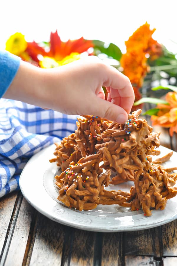 Hand reaching for haystack cookies on plate