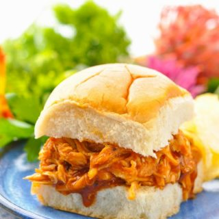 Pulled BBQ Chicken in Crock Pot served on a sandwich roll and placed on a blue plate
