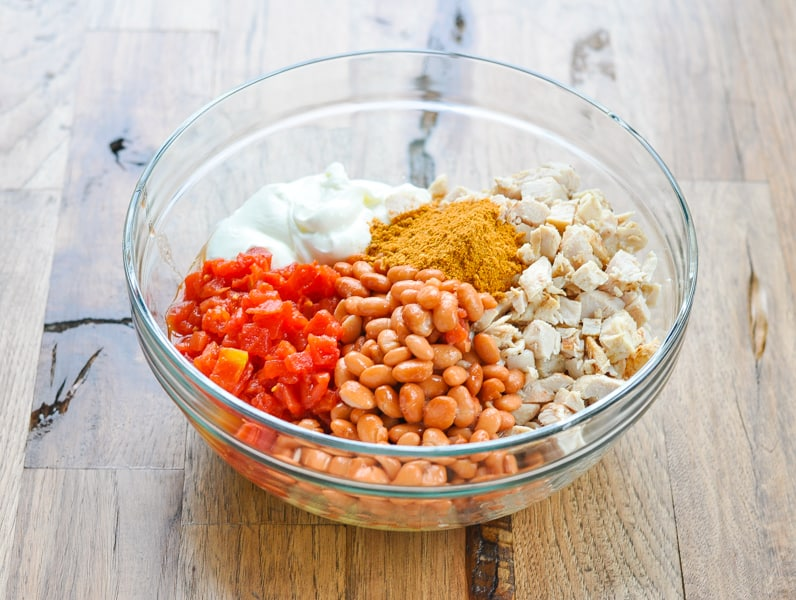 Filling ingredients for chicken easy taco casserole in glass mixing bowl
