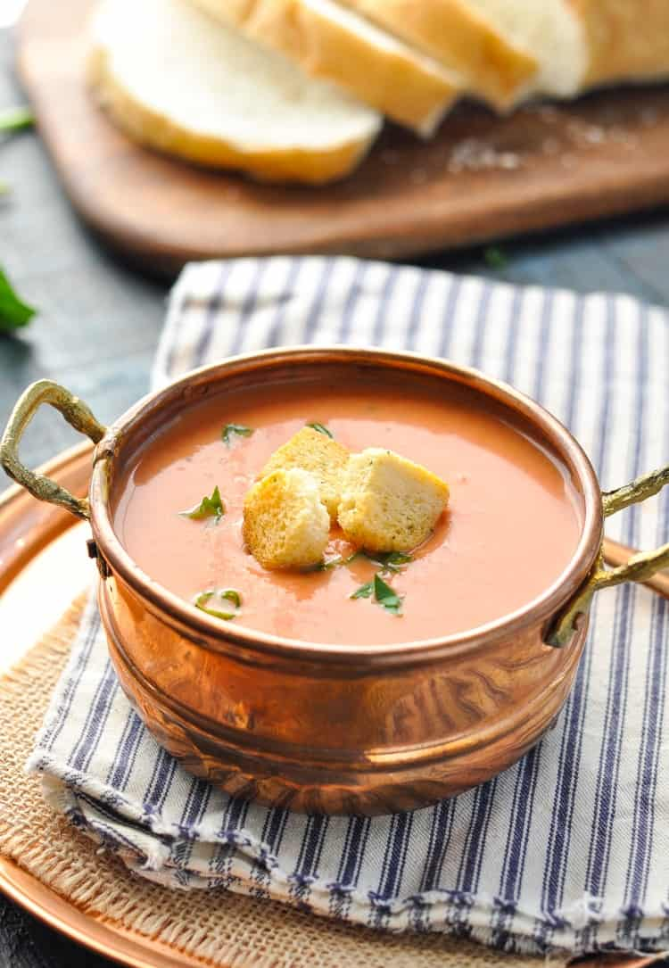 A tomato and basil soup in a copper bowl sitting on a stripped dish towel