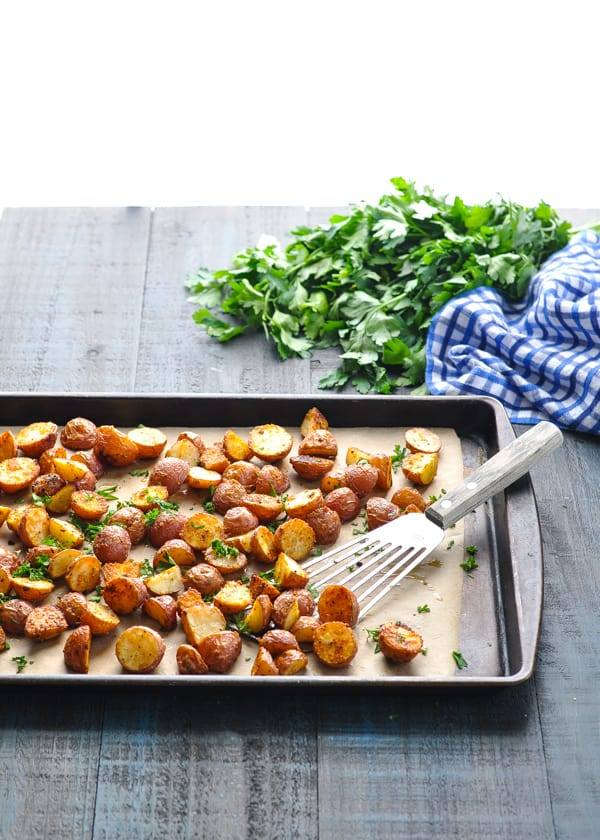 Oven Roasted Potatoes on a baking sheet with spatula and garnished with parsley