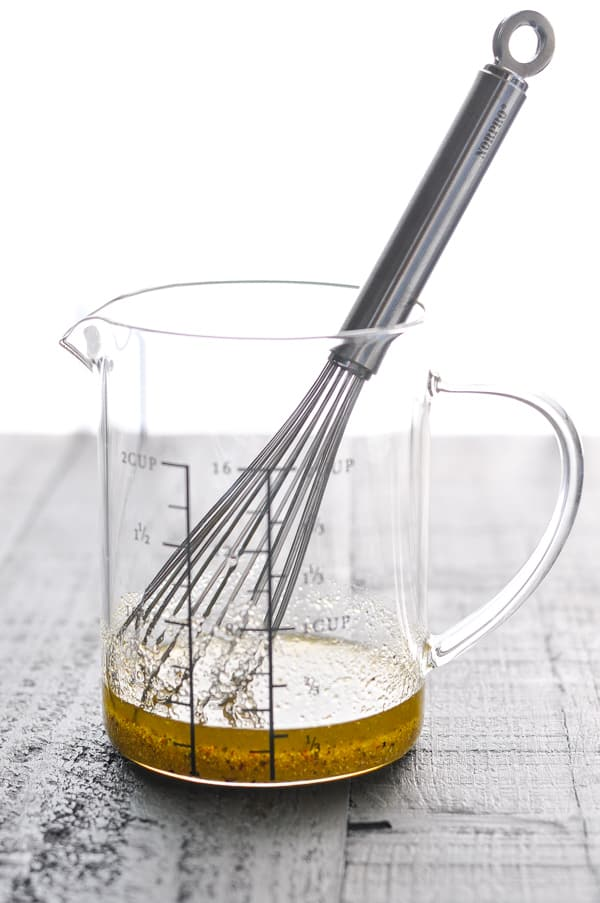 Olive oil and herb seasonings in glass measuring cup with whisk