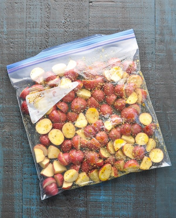 Red potatoes and seasoning mix in large ziploc bag