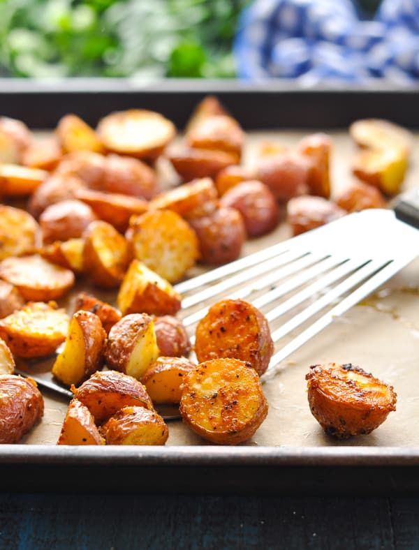 Crispy Oven Roasted Potatoes with spatula on baking sheet