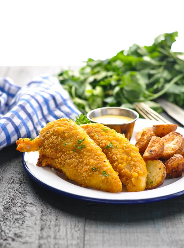 Crispy chicken tenders recipe on plate with potatoes