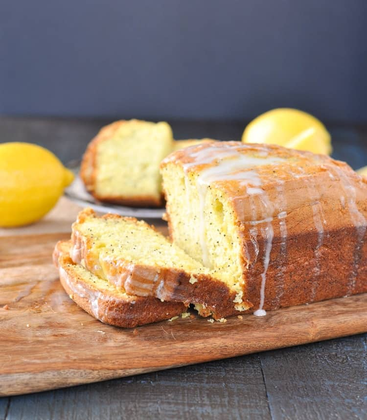 A close up of a loaf of lemon poppy seed bread drizzled with a glaze