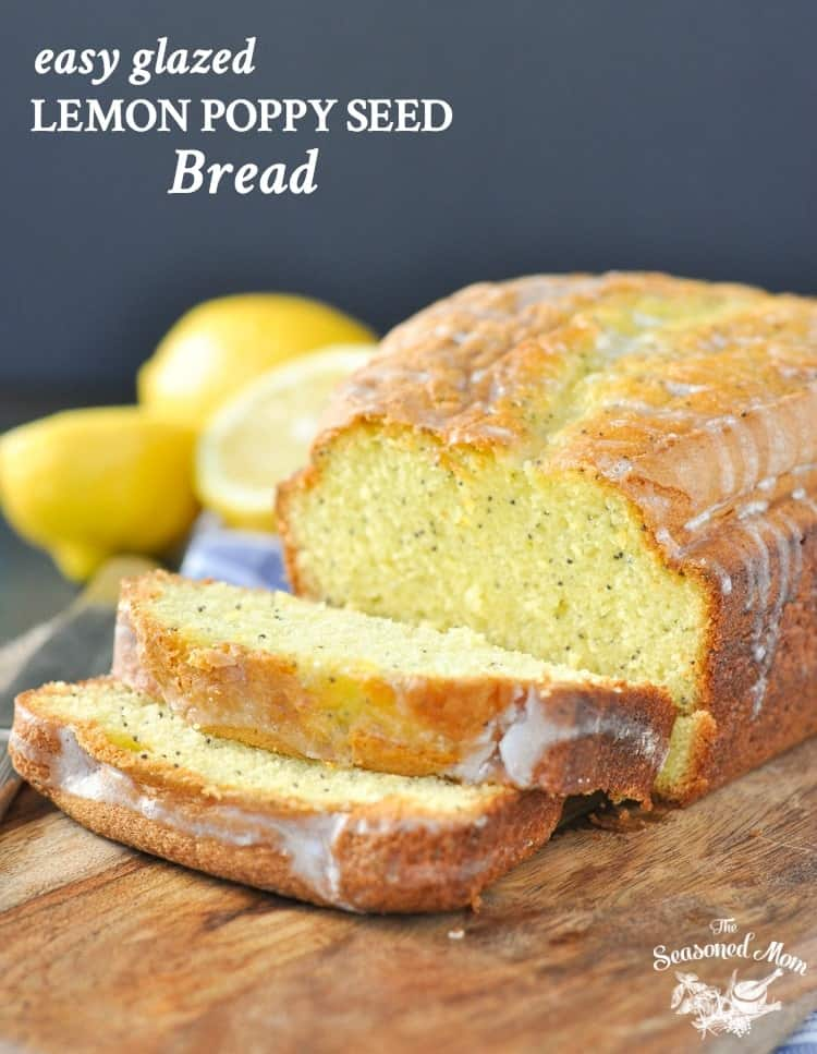 A photo of a lemon poppy seed bread loaf on a wooden board with a few slices cut
