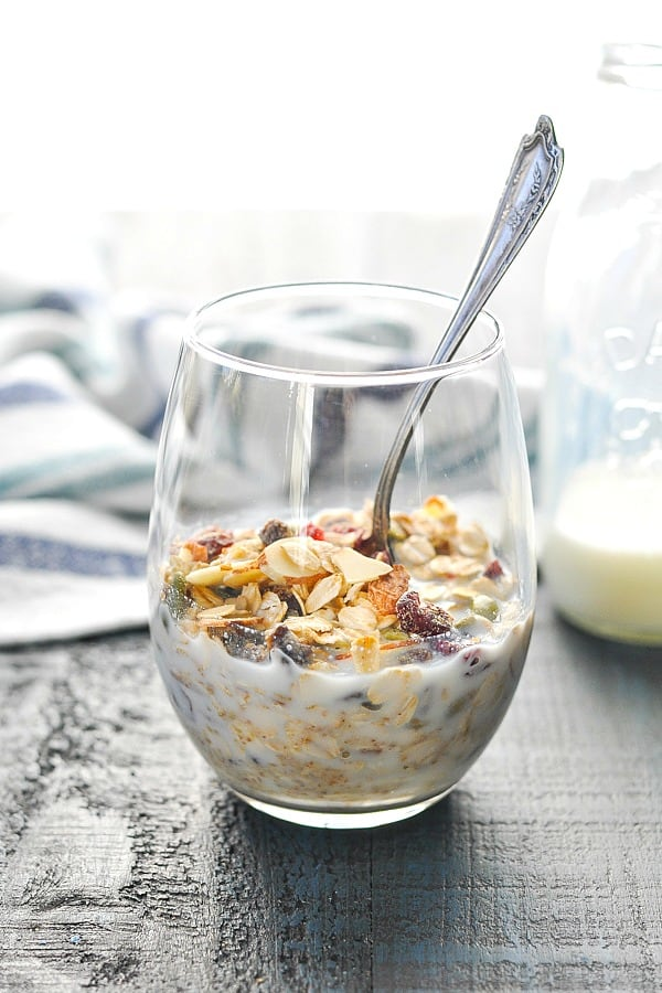 Front view of muesli in a glass with milk and a spoon