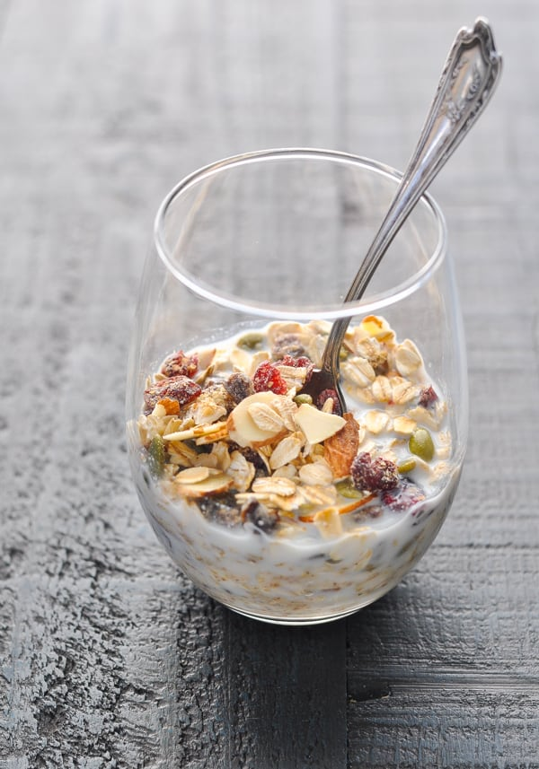 Muesli with milk in a glass with a spoon
