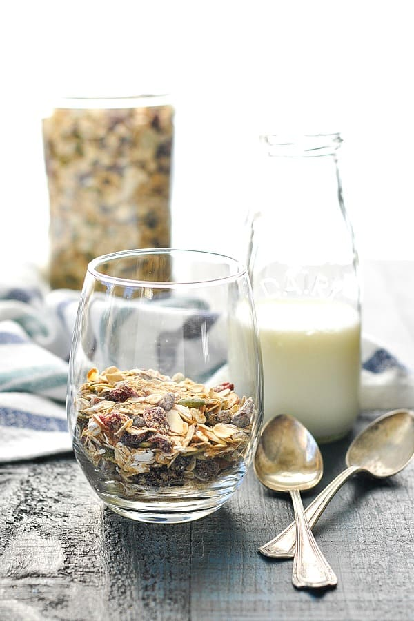 Muesli in a glass with milk and spoons in background