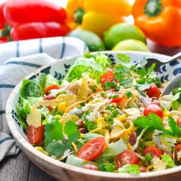A Mexican chicken salad in a large bowl sitting on a wooden surface
