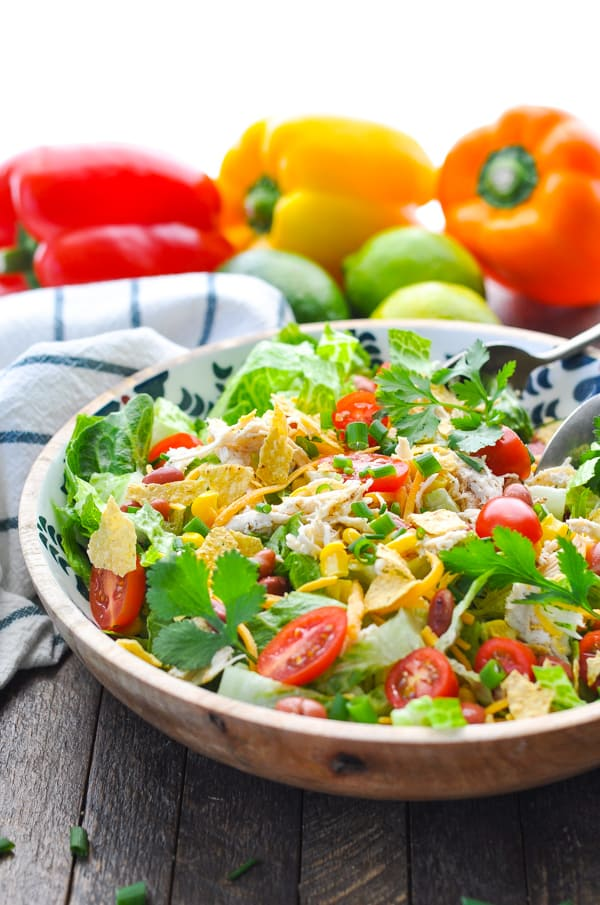 A mexican chicken salad in a bowl topped with tortilla chips, cheese and tomatoes