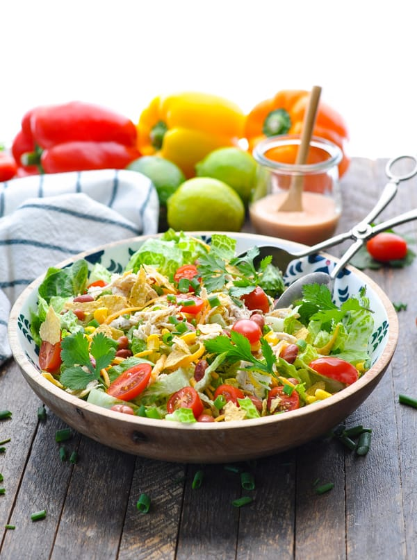 A bowl of Mexican chicken salad sitting on a wooden surface with bell peppers in the background