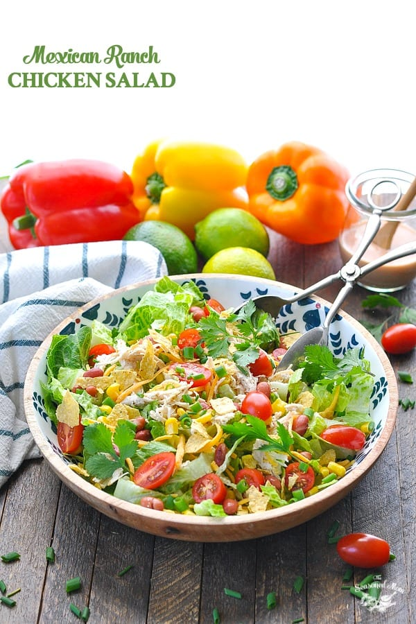 A large salad bowl filled with a Mexican chicken salad and salad tongs