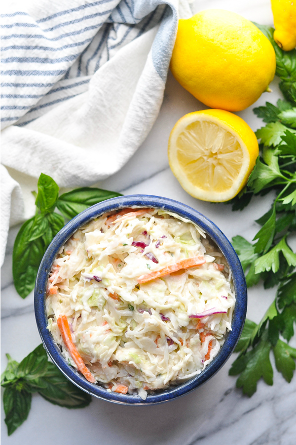 Overhead shot of creamy coleslaw in a blue serving bowl with herbs and lemons surrounding