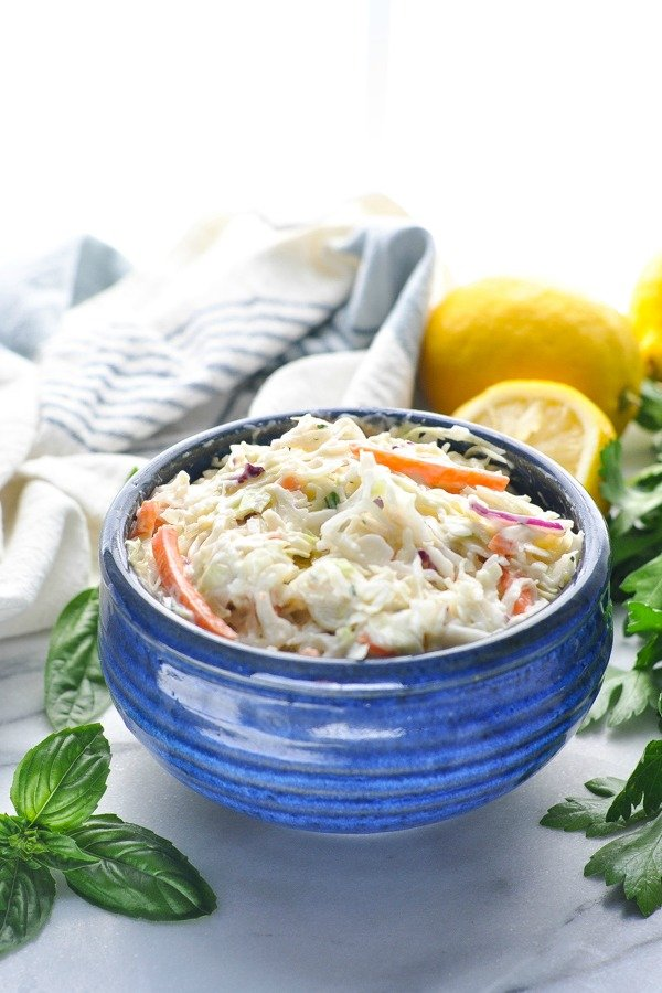 Front shot of shredded cabbage and carrots tossed with creamy coleslaw dressing