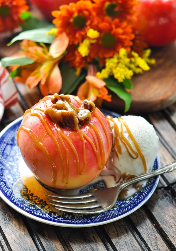 Baked apple on a plate with vanilla ice cream drizzled with caramel sauce