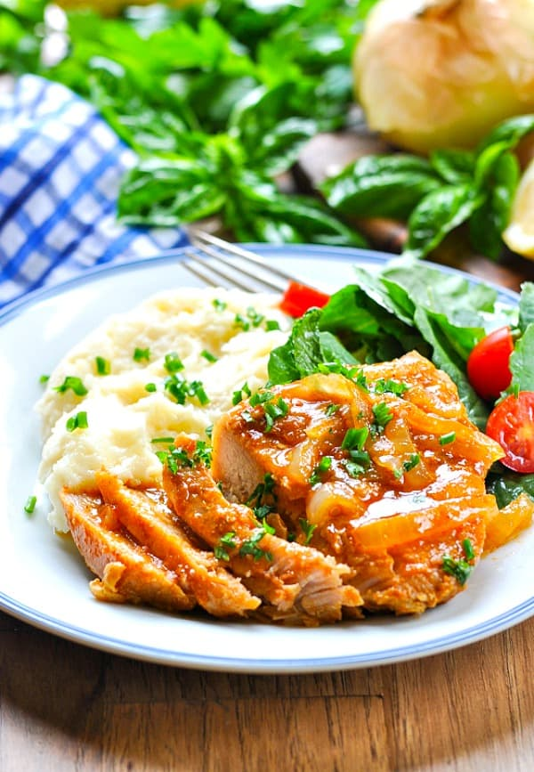 Sliced Crock Pot Smothered Pork Chops on a plate with mashed potatoes and salad