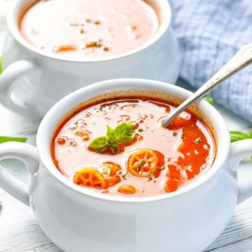 Two white bowls filled with tomato marinara soup topped with basil