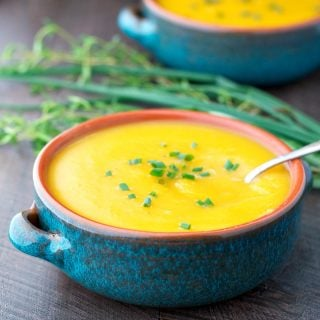 Butternut squash soup in a large blue bowl with a spoon