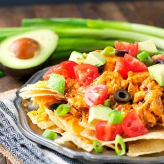 Plate of crock pot chicken nachos piled high with toppings