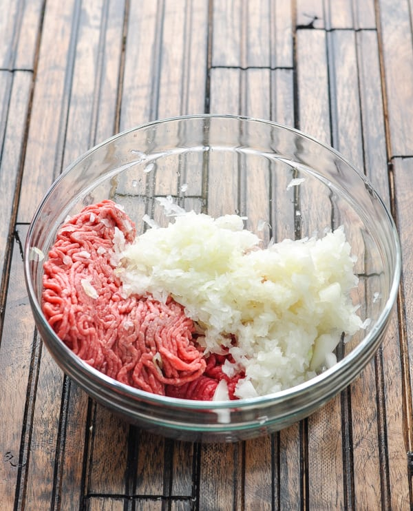 Ground beef and grated onion in glass mixing bowl