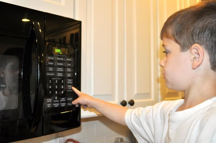 A boy putting on a microwave