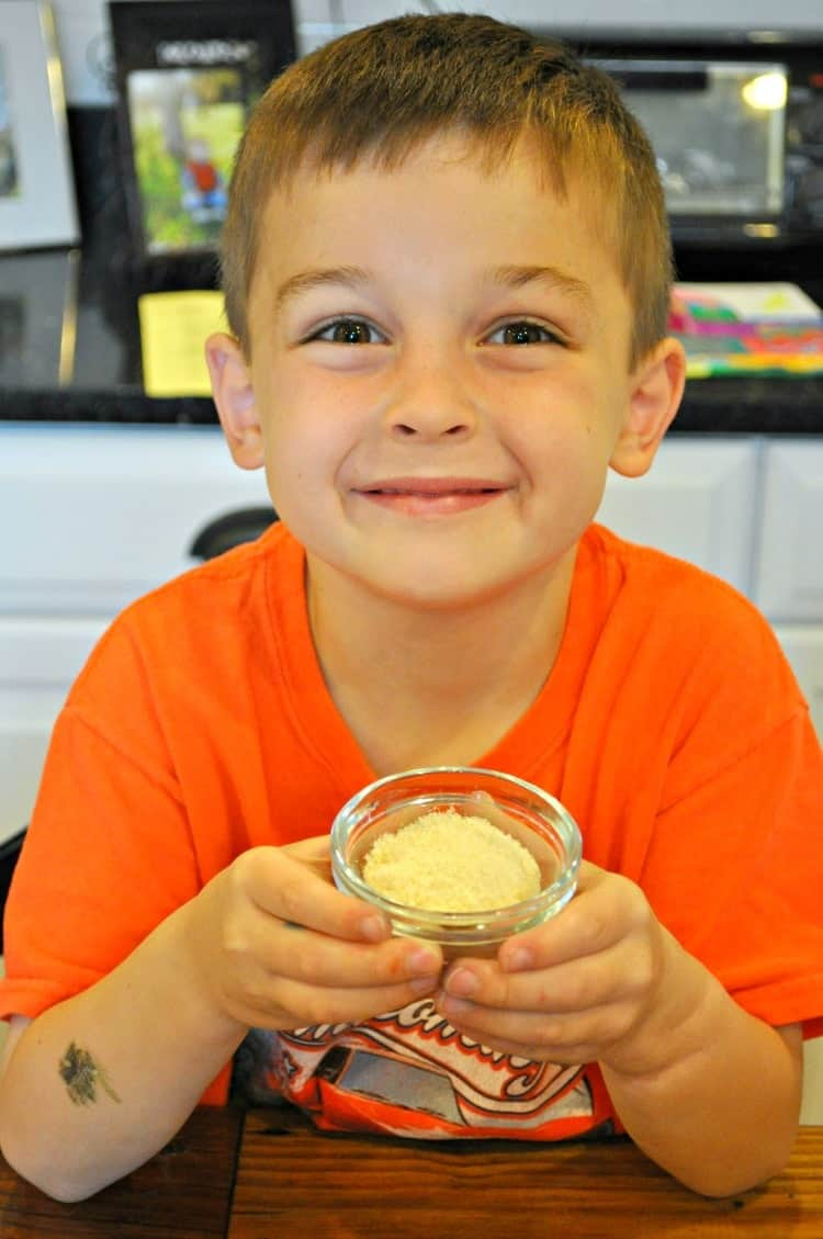 A boy holding spices in a small glass bowl