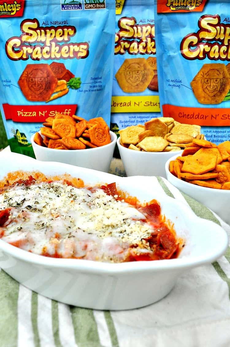 Microwave Pizza Dip in a white dish the packets of crackers in the background