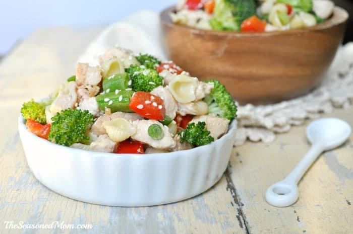 Sesame Chicken Pasta Salad in a white bowl with a spoon at the side