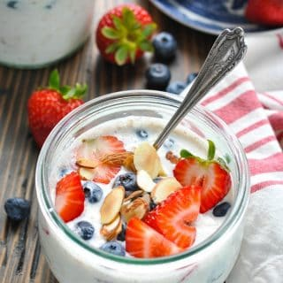 Fresh strawberries and blueberries on top of a bowl of overnight oatmeal
