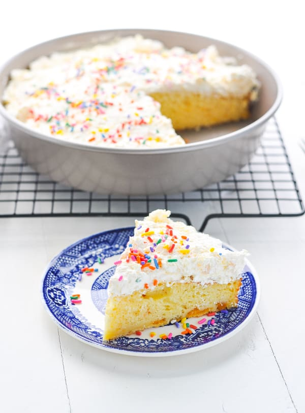 Slice of easy Orange Cake on a blue and white plate with sprinkles.