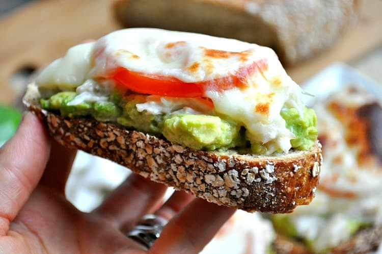 A hand holding a crab melt with avocado and tomato