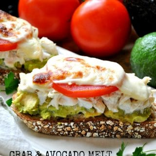 An open faced avocado and crab melt topped with a tomato on a plate