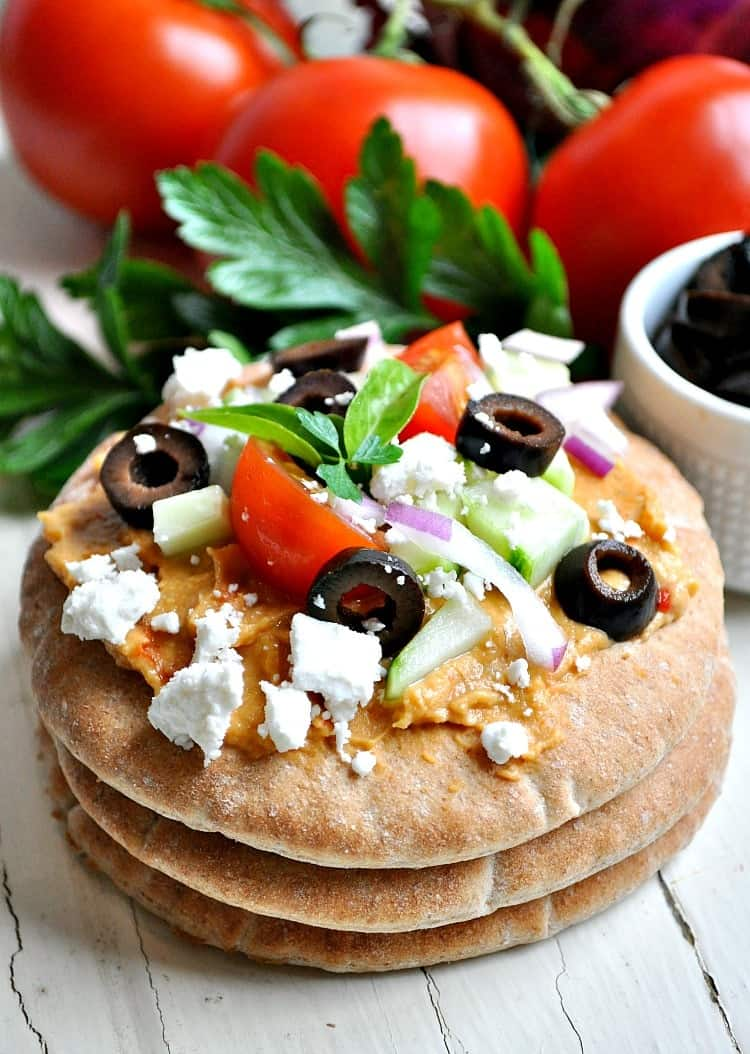 A stack of three pita bread bites topped with feta, olives and tomato