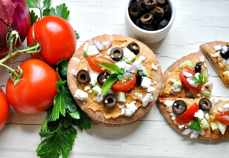 An overhead shot of Greek pita bread bites topped with feta, olives and tomato